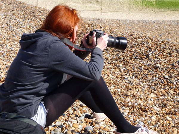 Image of girl taking beach photographs with camera