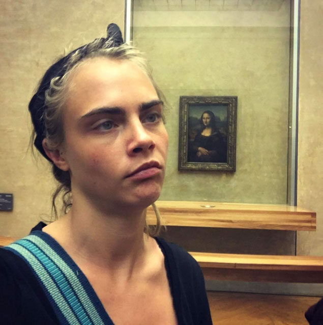 Photograph of Cara Delevingne posing by the Mona Lisa painting