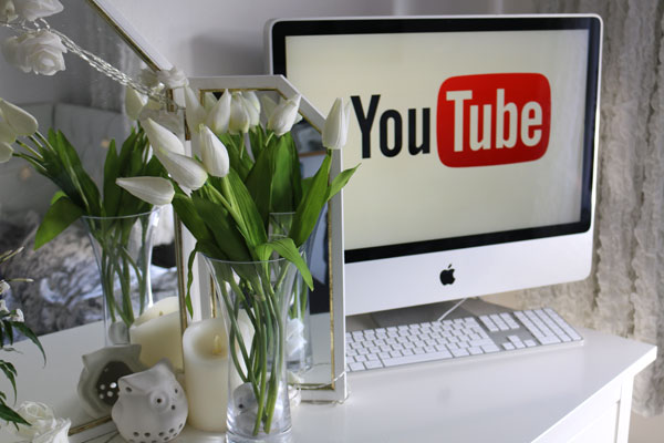 Photo of computer with YouTube channel logo
