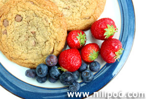 Picture of chocolate chip cookies with strawberries and blueberries