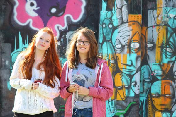 Teenage girls by a wall with graffiti