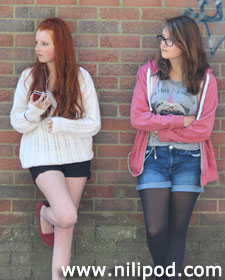 Teenage girls leaning against a brick wall