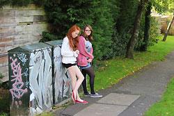 Girls standing by graffiti / pathway