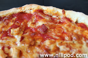 Picture of homemade pizza crust, with chunks of ham