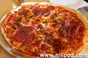 Photo of a homemade pepperoni pizza, sliced and ready to eat