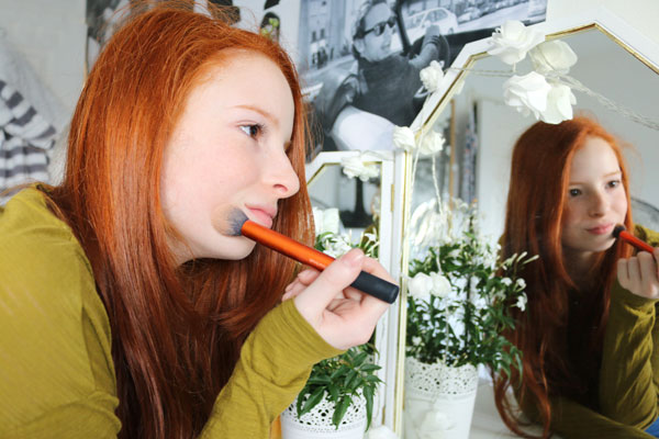 Picture of girl putting on makeup in mirror