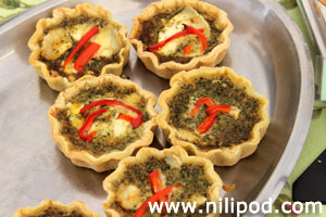 Photo of mini quiches with slices of red pepper