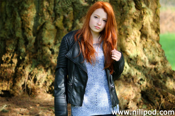 Photo of girl with red hair standing by tree trunk
