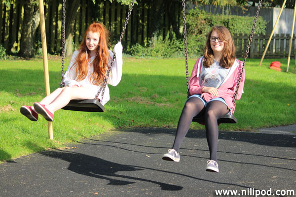 Girls playing on the swings at the local playground