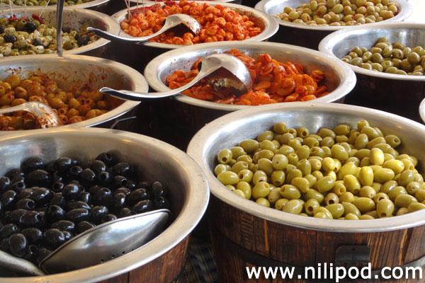 Photo of olives being sold in barrels at food market