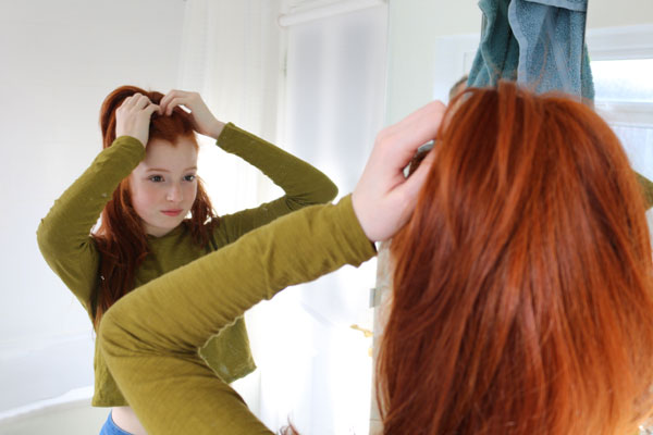 Photo of girl putting hair up